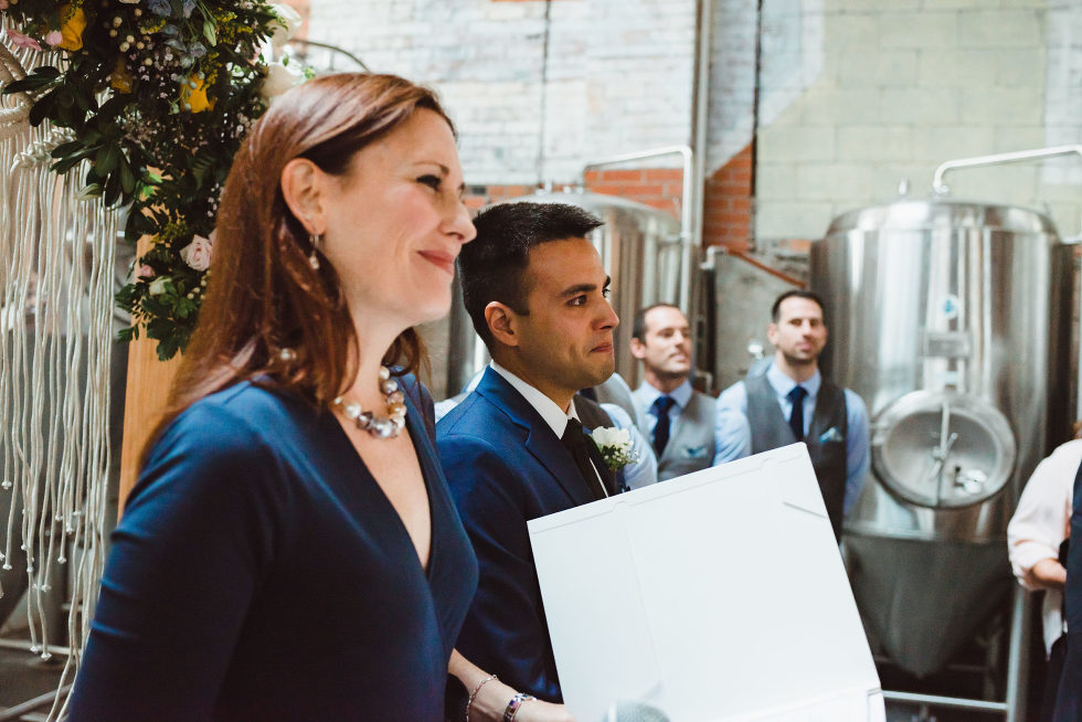 wedding officiant and groom smiling at the alter in front of brewing tanks Toronto Junction Craft Brewing wedding photography