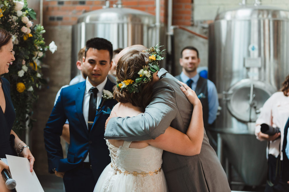 bride hugging her father after he walked her down the aisle Toronto Junction Craft Brewing wedding photography