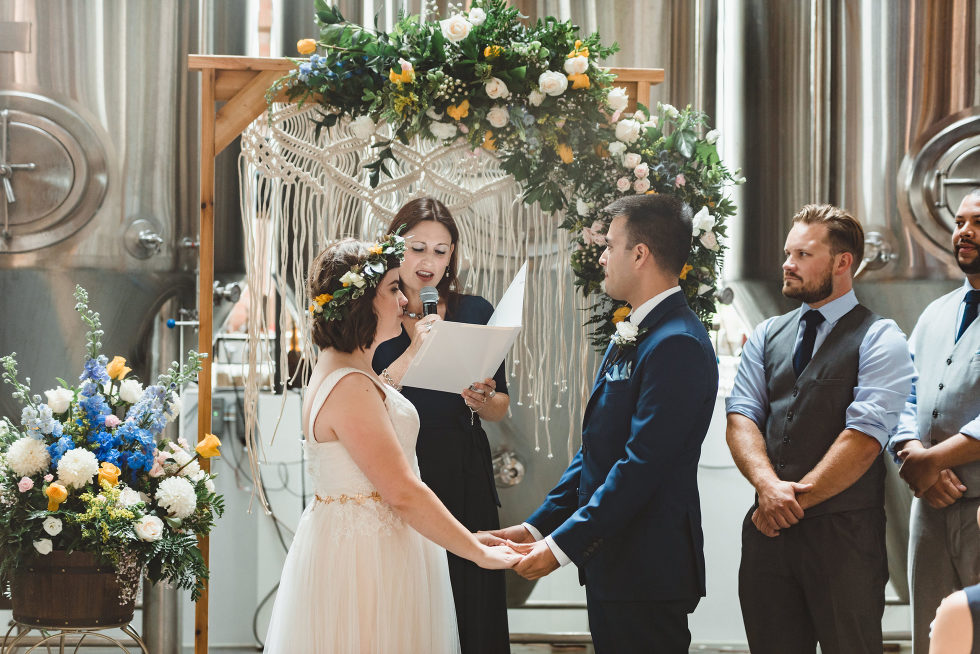 bride and groom holding hands as officiant performs wedding ceremony with brewing tanks in the background Toronto Junction Craft Brewing