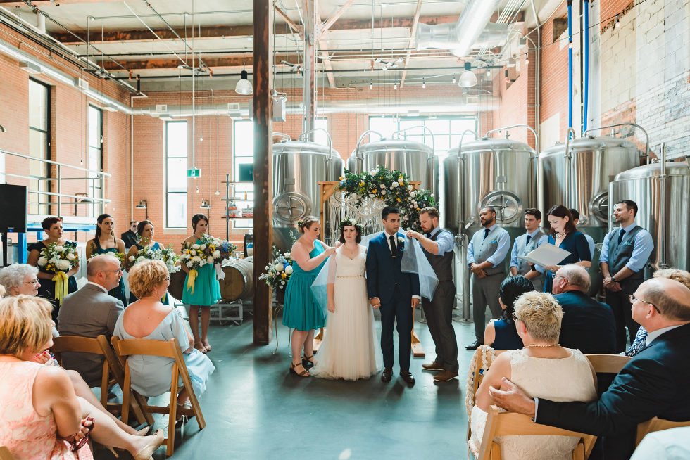 wedding ceremony in an old brewery with brewing tanks behind the alter Toronto Junction Craft Brewing