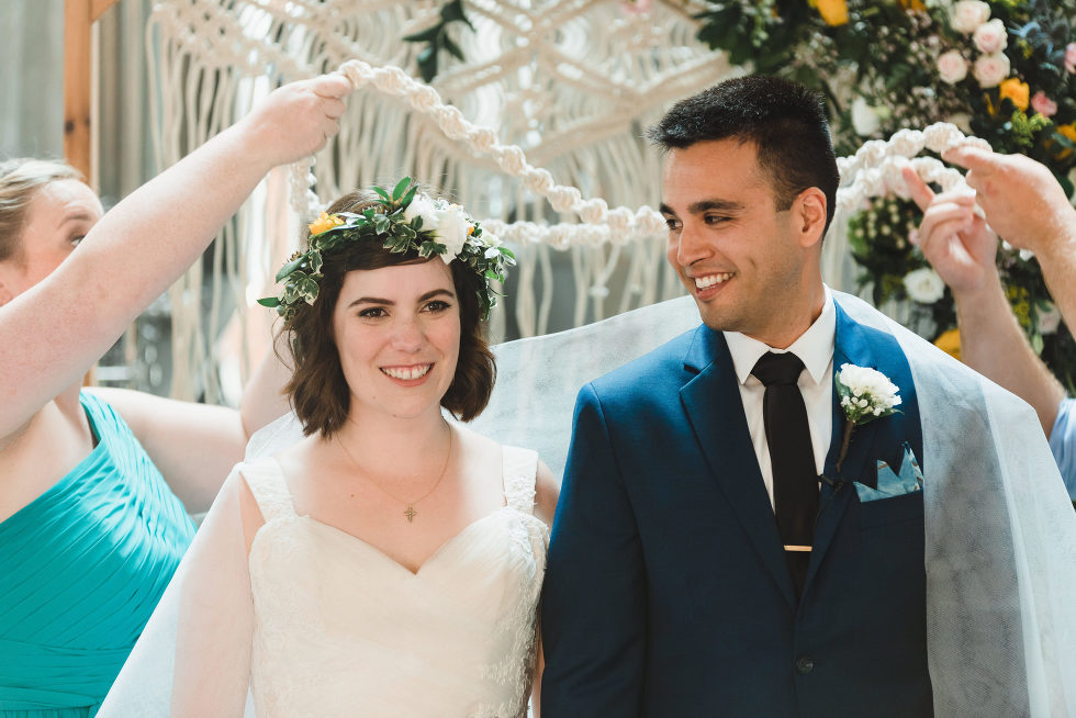 bride and groom smile as white decorations are placed upon them during ceremony Toronto Junction Craft Brewing wedding photographer Gillian Foster