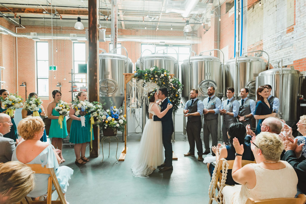 bride and groom kiss during wedding ceremony in an old brewery with brewing tanks behind the alter Toronto Junction Craft Brewing