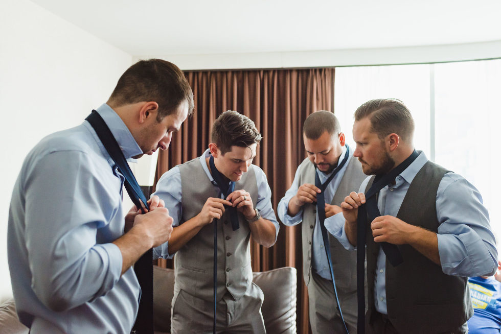 groomsmen in blue dress shirts and grey vests and pants stand in a circle as they all do up their neck ties Toronto Junction Craft Brewing wedding