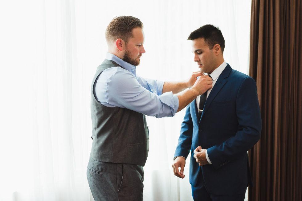 groomsman helping tighten grooms black neck tie Toronto brewery wedding photography