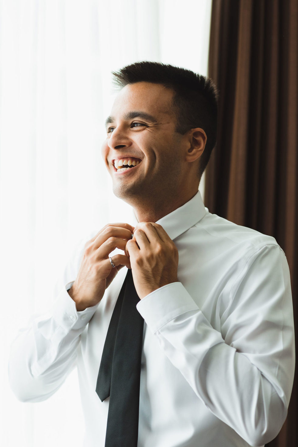 groom smiling while tying his black neck tie Toronto brewery wedding photography