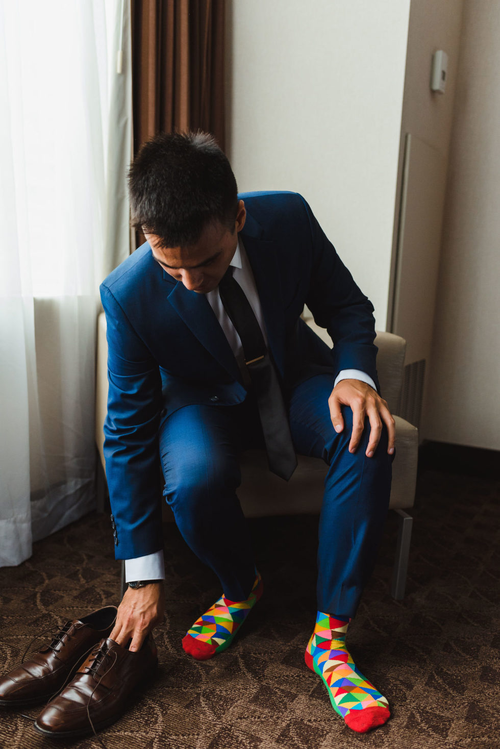 groom in blue suit and multi-coloured socks sitting in a chair about to put on brown dress shoes Toronto brewery wedding photography