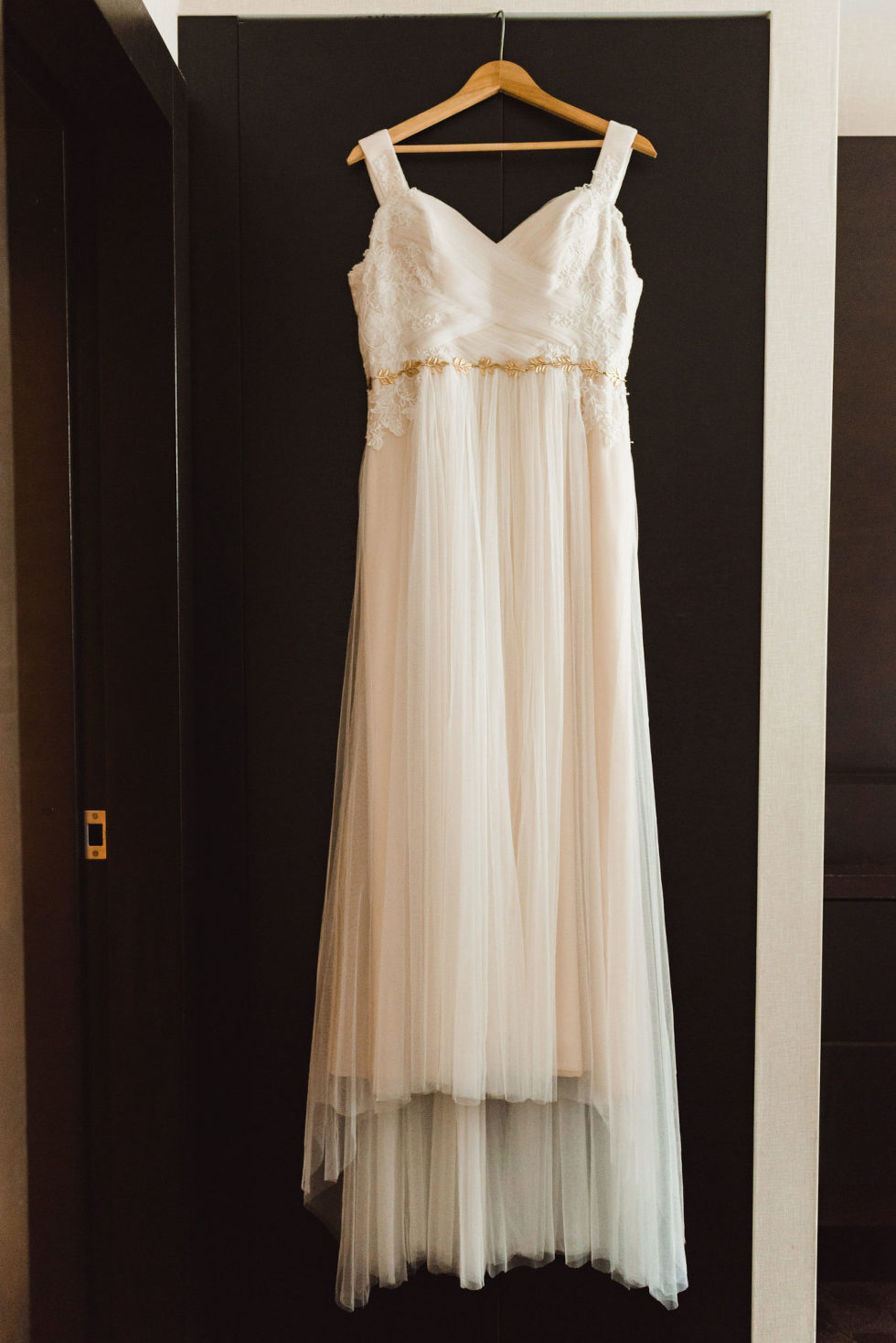 white wedding dress hanging on the back of a brown door Toronto brewery wedding photography
