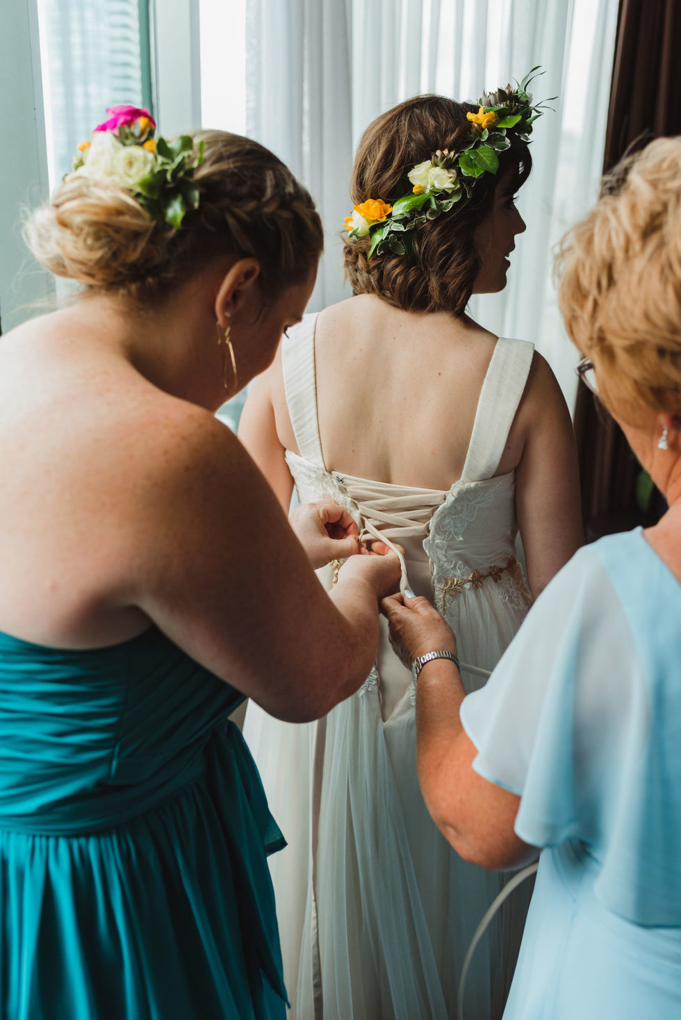 bride wearing flower crown having her gown tied up in the back by bridesmaid and mother Toronto Junction Craft Brewing wedding photography