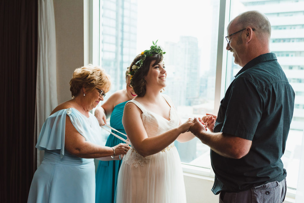 bride having her wedding dress tied up in the back by bridesmaid and mother while she holds her fathers hands in front of her Toronto wedding photography