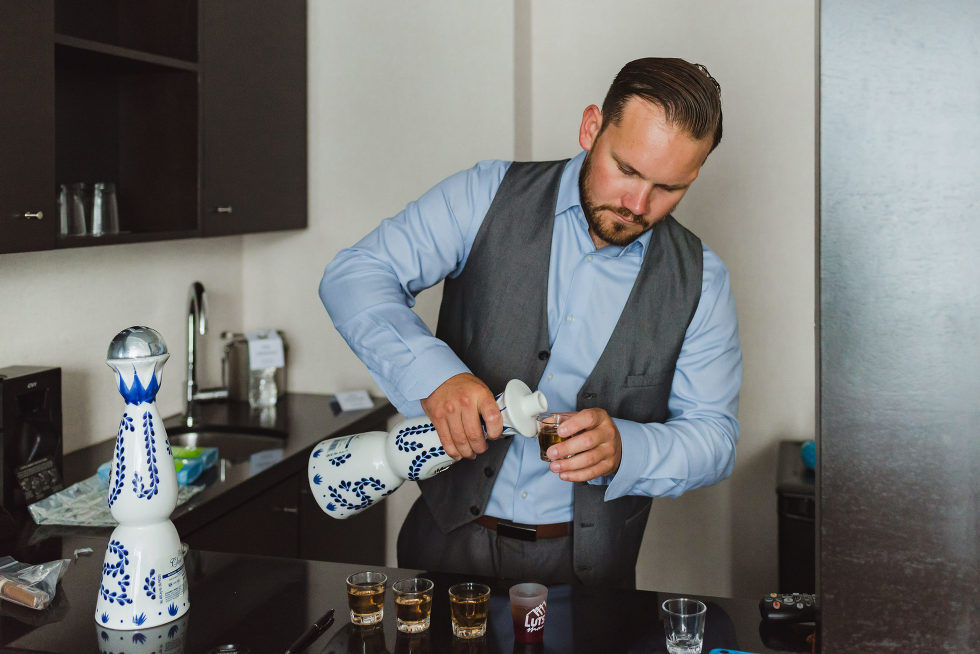 groomsman in blue dress shirt and grey vest pouring shots into 5 glasses Toronto Junction Craft Brewing photography
