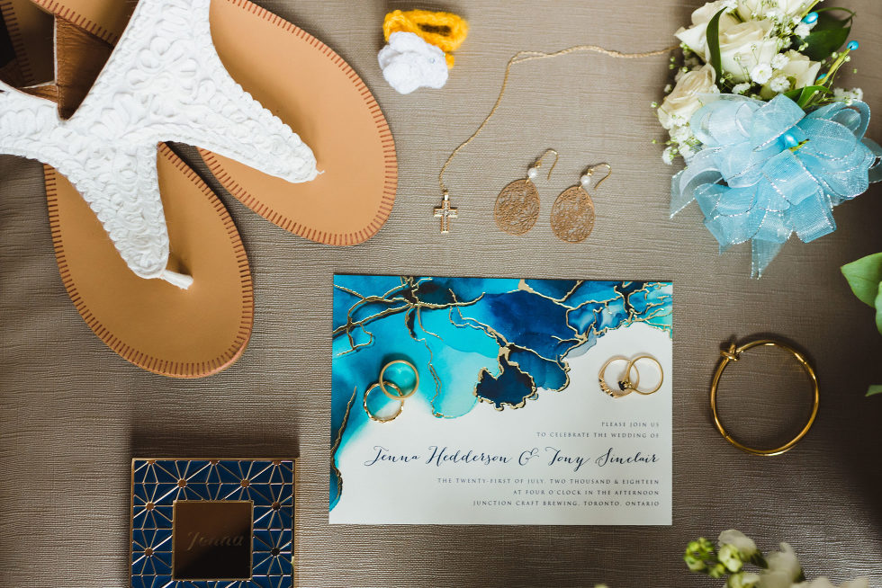wedding invitation surrounded by wedding rings, jewellery, boutonniere, and white and brown sandals Toronto Junction Craft Brewery wedding