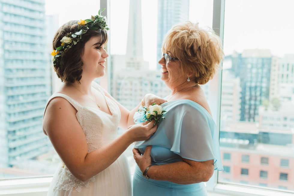 bride with flower crown placing boutonniere on her mothers blue dress Toronto brewery wedding photography