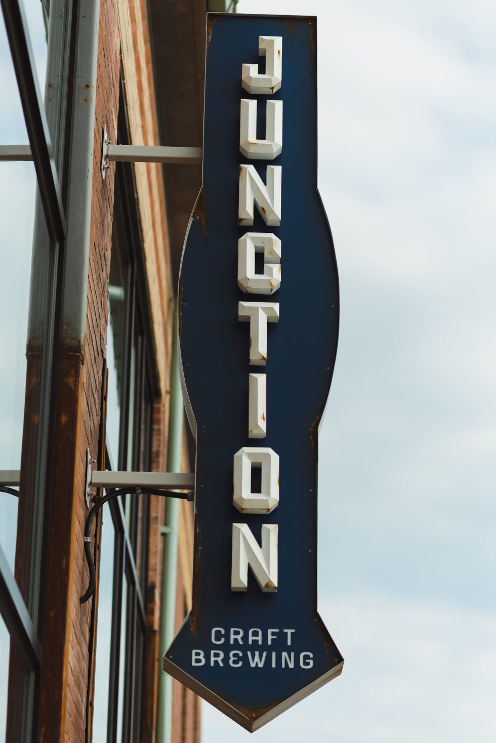 A blue and white brewery sign hanging off side of brick building that read Junction Toronto brewery wedding photography