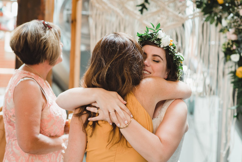 bride hugging a wedding guest Junction Craft Brewing Toronto wedding photographer Gillian Foster