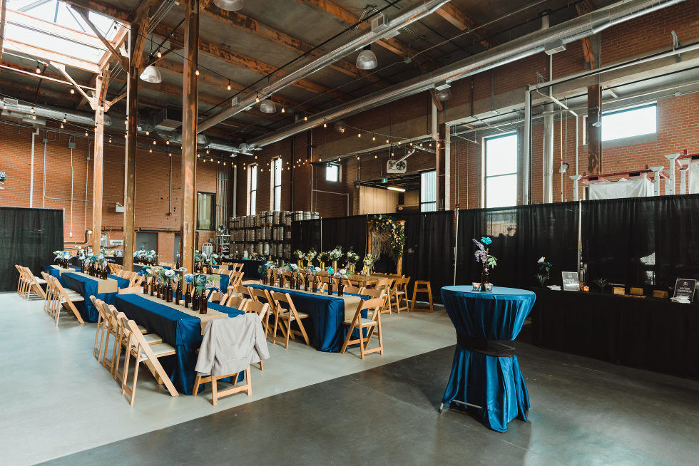 wedding reception tables set up in a craft brewery Toronto Junction Craft Brewing