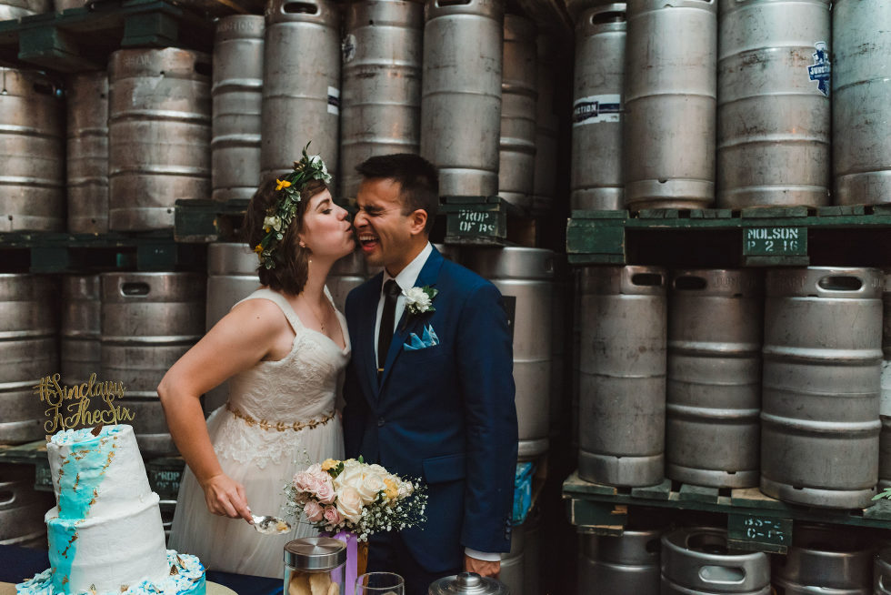 bride kissing groom on his cheek while she cuts the wedding cake with kegs of beer stacked behind them Junction Craft Brewing wedding photography