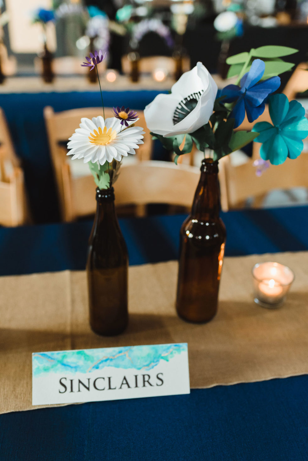 "brown beer bottles with flowers placed in them on wedding reception table with a card reading ""Sinclairs"" in front of them Toronto Junction Craft Brewing wedding"