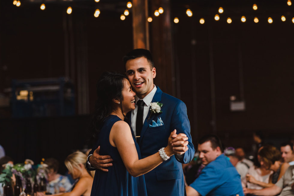 wedding guests watch from tables as groom and his mother share a dance Junction Craft Brewing wedding photography