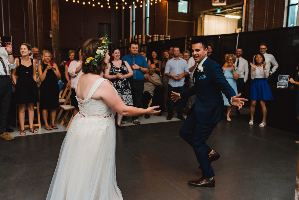 wedding guests watch as bride and groom share a first dance Junction Craft Brewing wedding photography