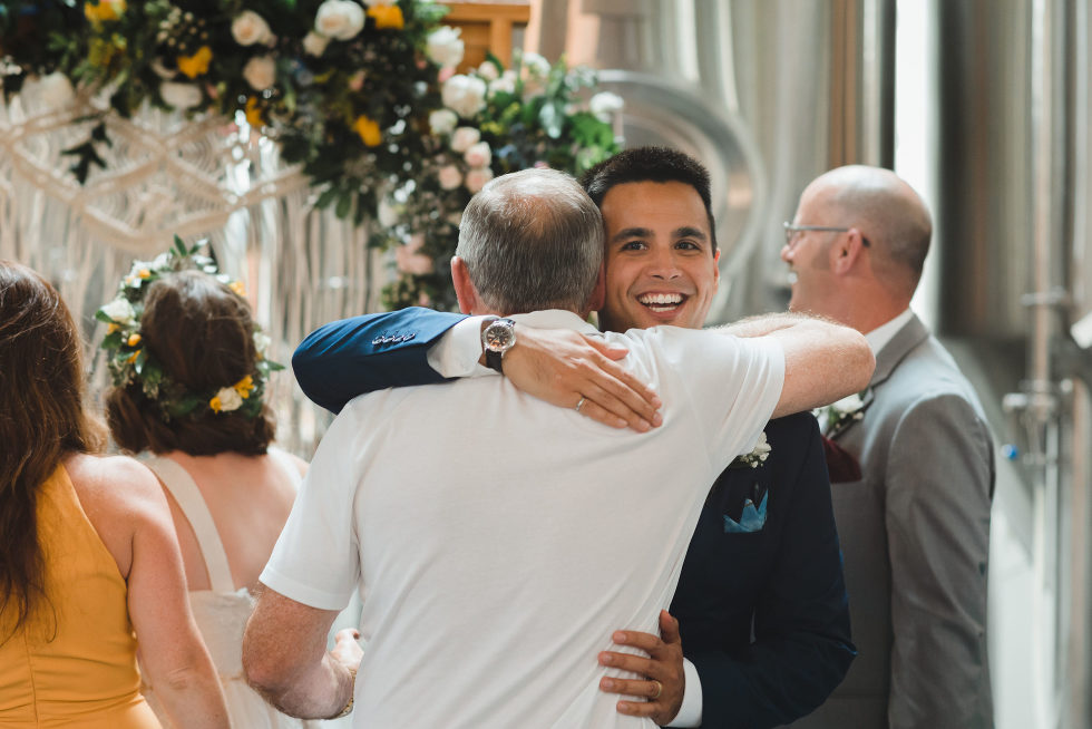 groom hugging a wedding guest Junction Craft Brewing Toronto wedding photographer Gillian Foster