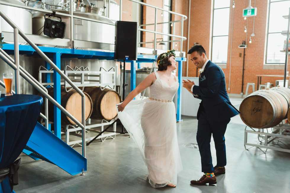 bride and groom dance as they enter wedding reception surrounded by beer barrels and brewing equipment Junction Craft Brewing wedding photography Toronto