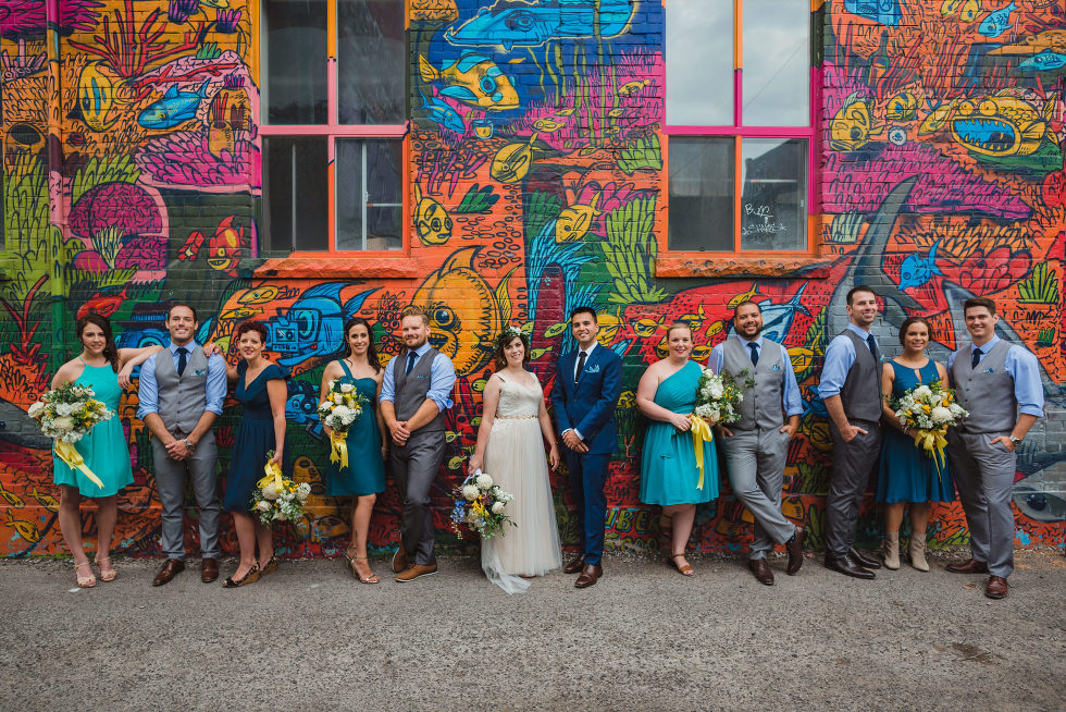 bride and groom leaning up against a graffitied wall with their wedding party Toronto Junction Craft Brewing wedding