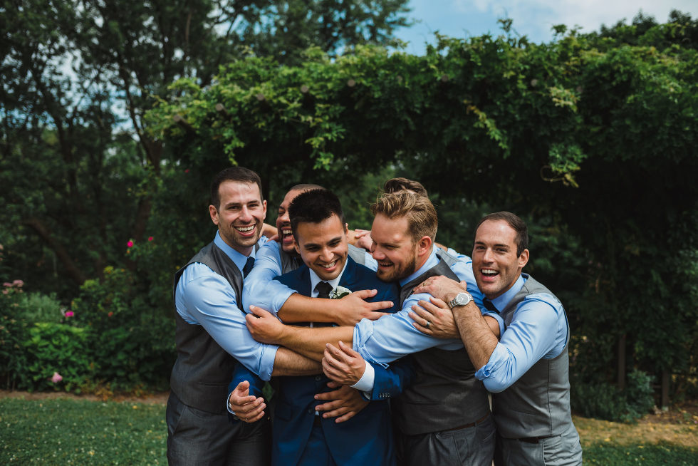 groom smiling as his groomsmen all wrap their arms around him in a park Toronto Junction Craft Brewing wedding