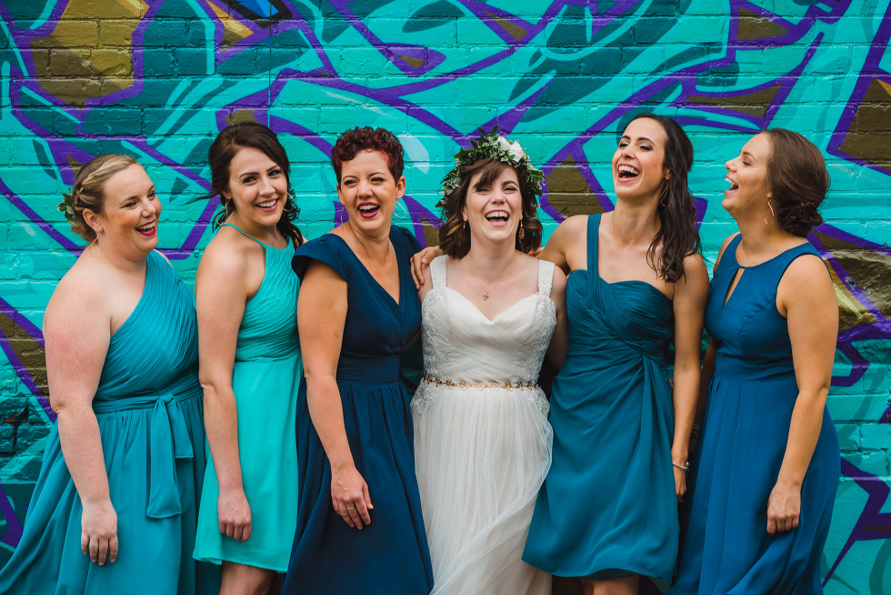 Bridal party in teal dresses laughing in Graffiti alley Toronto