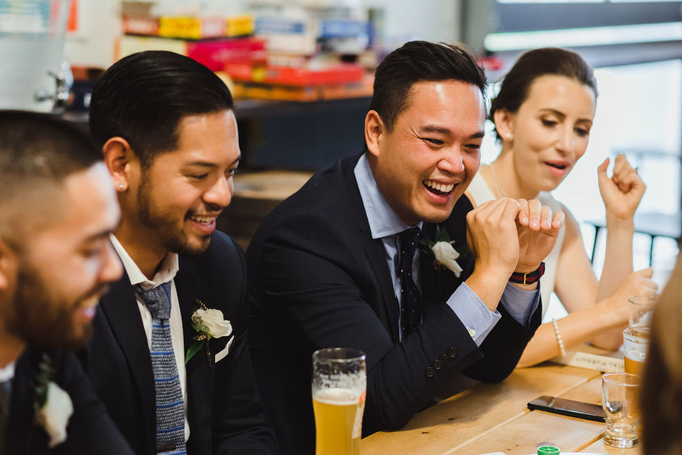 bride, groom, and wedding guests crowded around a picnic table with pints of beer at Henderson