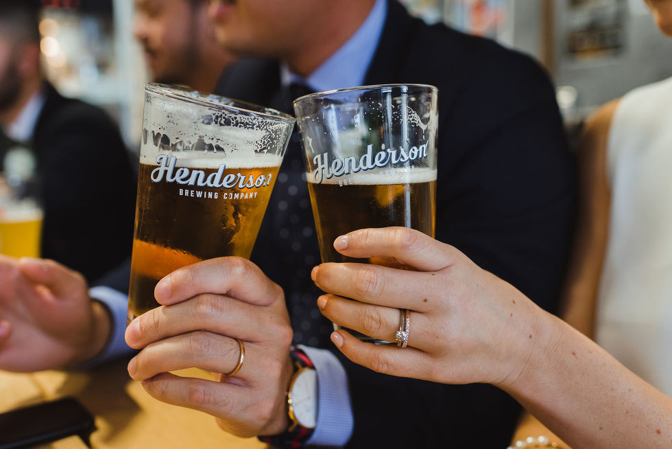 bride and groom toasting each other with pints of beer at Henderson