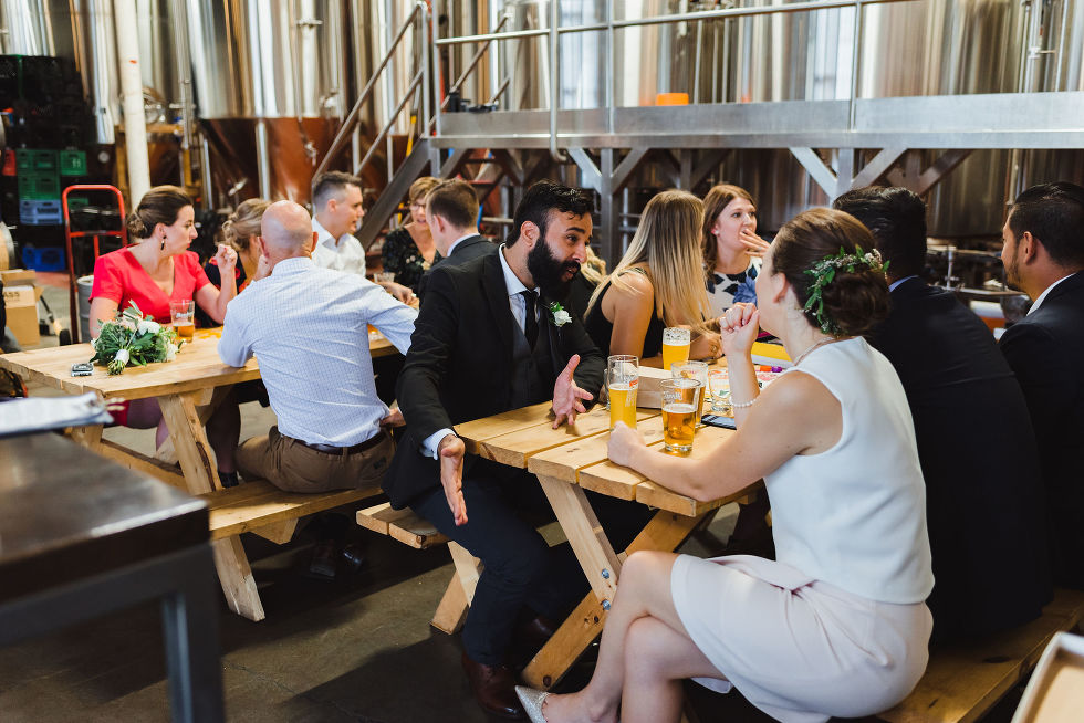 wedding guests sitting at picnic tables playing games and drinking pints of beer at Henderson