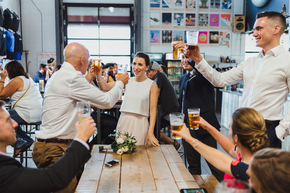 bride and groom toasting the wedding guests at a picnic bench in Henderson Brewing Company Toronto wedding