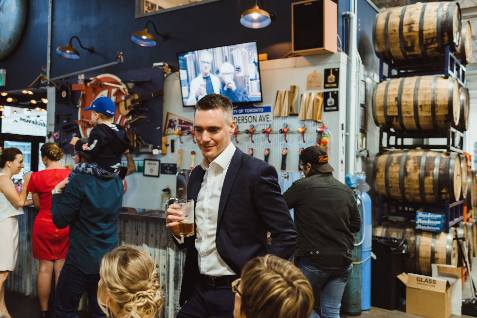 wedding guests holding pints with wooden barrels and taps behind them Henderson