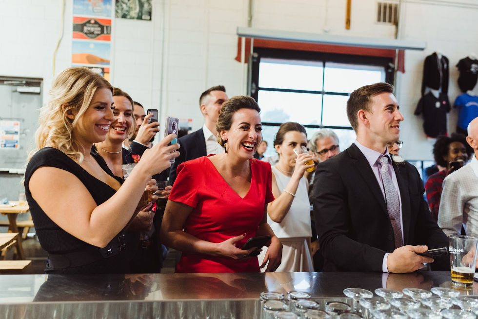 wedding guests and bride laughing and drinking pints at the bar in Henderson