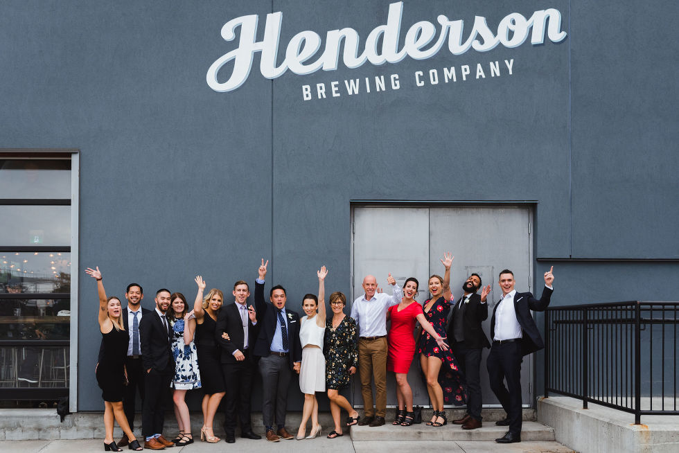 wedding guests with their arms in the air standing out front of the Henderson Brewing Company building Toronto wedding photography
