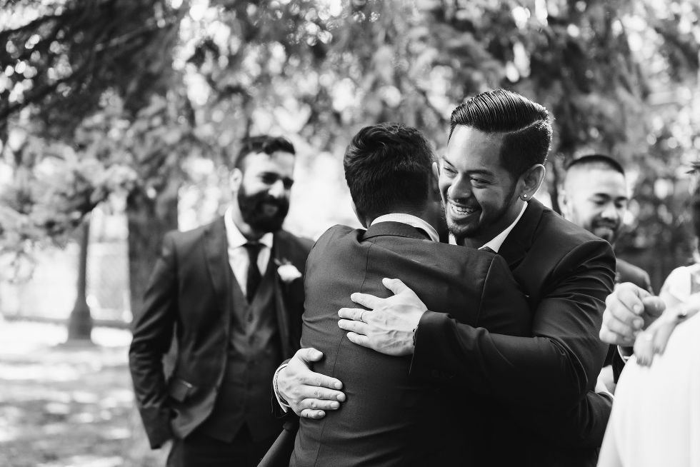 groomsman hugging groom during wedding ceremony in Trinity Bellwoods Park Toronto
