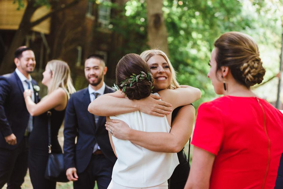 bride hugging bridesmaid during wedding ceremony in Trinity Bellwoods Park Toronto