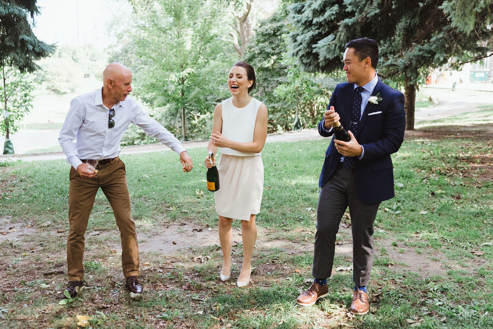bride and groom opening champagne with her dad reaching over in Trinity Bellwoods Park Toronto wedding ceremony