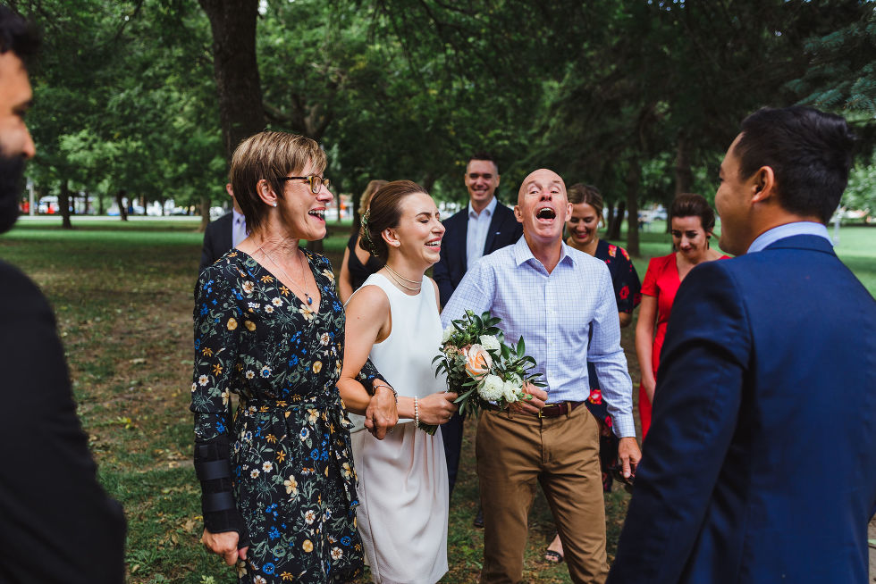 bride and her parents laughing while they are escorting her down the aisle to the ceremony in Trinity Bellwoods Park Toronto Canada