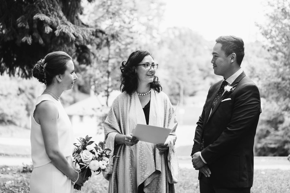 bride and groom stand before officiant as wedding ceremony begins Trinity Bellwoods wedding Toronto