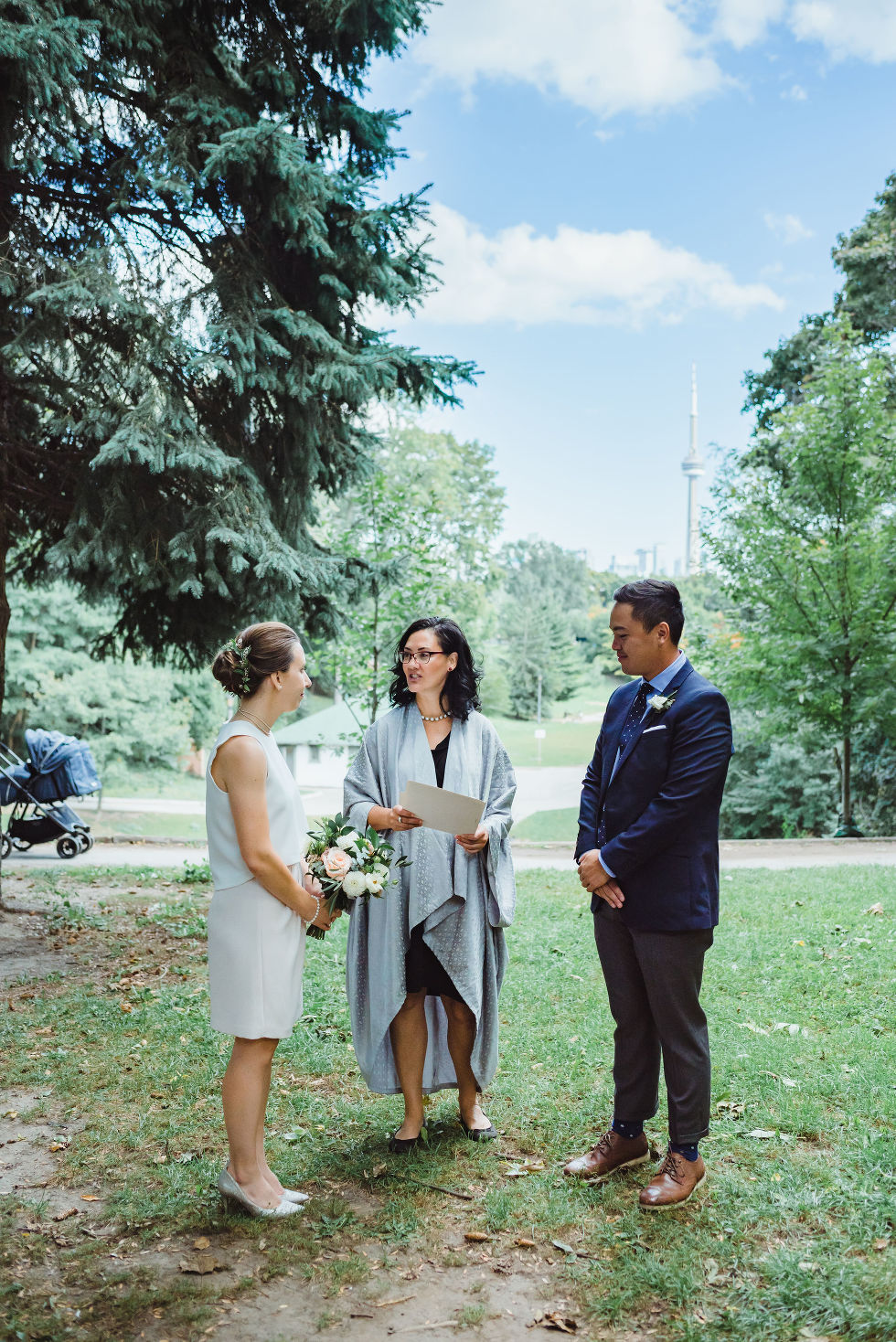 bride and groom stand before officiant during wedding ceremony Trinity Bellwoods wedding Toronto