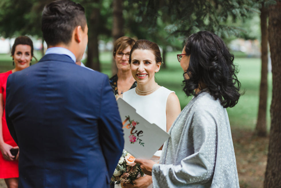 bride smiling at groom during wedding ceremony in Trinity Bellwoods Park Toronto Canada