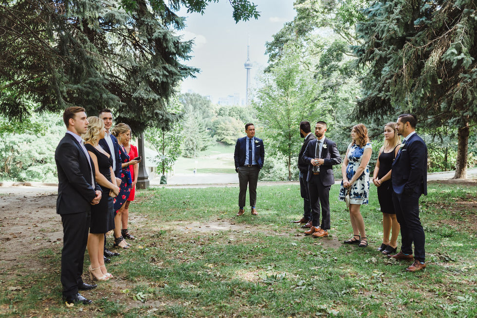 small wedding ceremony in Trinity Bellwood Park with view of CN tower behind them Toronto wedding