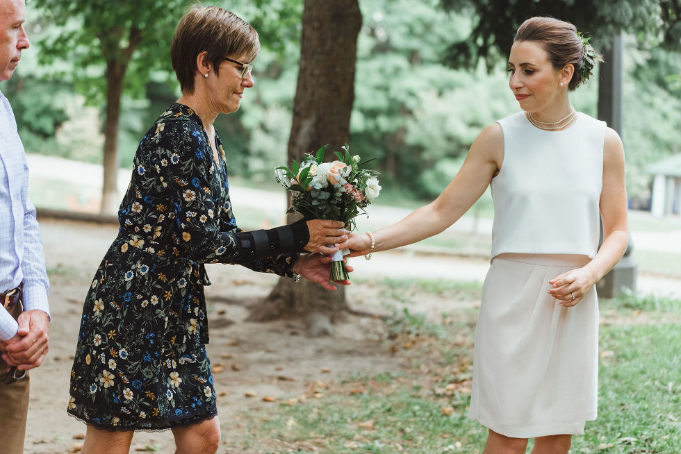 bride handing her mother her bouquet of flowers during wedding ceremony in Trinity Bellwoods Park Toronto