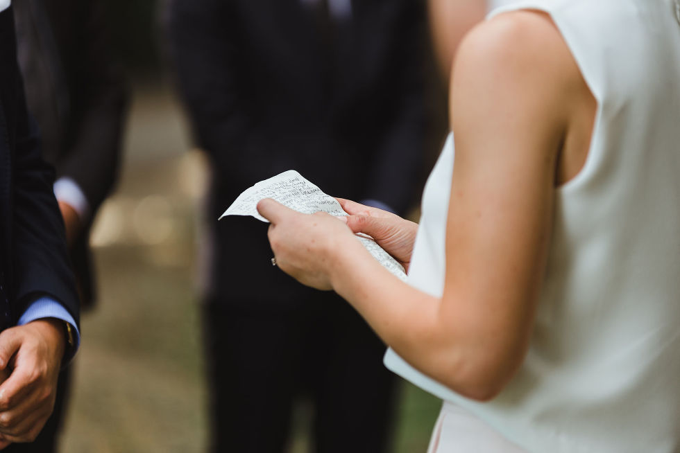 bride holding her nuptials written on a piece of white paper Trinity Bellwoods wedding Toronto