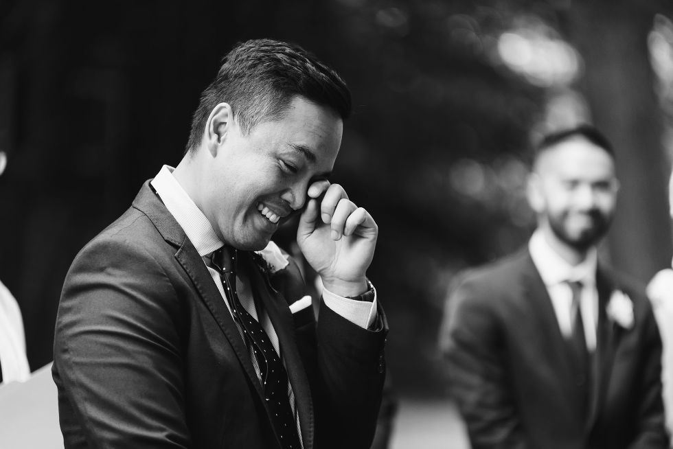 groom wiping a tear from his eye with his finger during wedding ceremony in Trinity Bellwoods Park Toronto