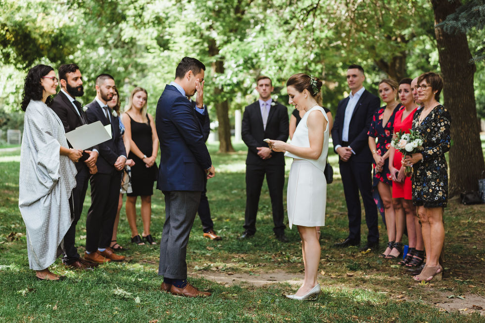 groom wiping a tear from his eye with his hand during wedding ceremony in Trinity Bellwoods Park Toronto