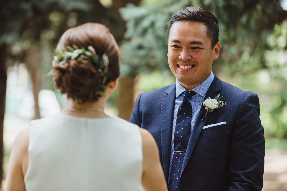 groom smiling at his bride during wedding ceremony in Trinity Bellwoods Park Toronto