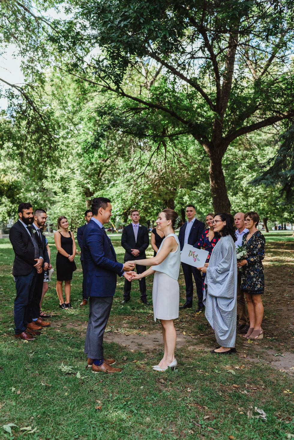 bride and groom holding hands during ceremony in Trinity Bellwoods Park Toronto