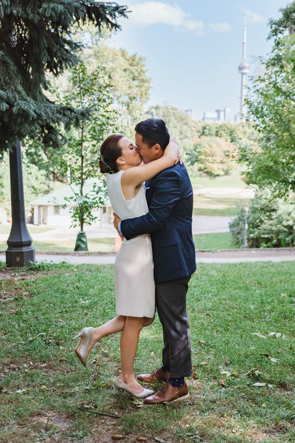 bride and groom kissing after wedding ceremony in Trinity Bellwoods Park with view of CN tower Toronto